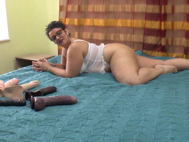 Une femme test sa collection de godes énormes